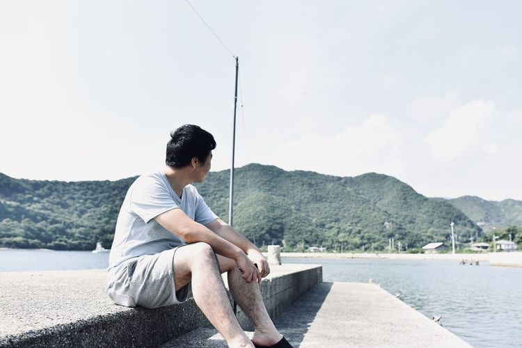 Man sitting on mountain looking at lake against sky