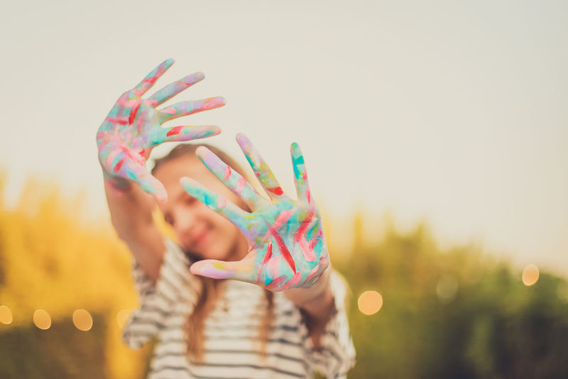 Close-Up Of Girl With Messy Painted Hands Against Clear Sky