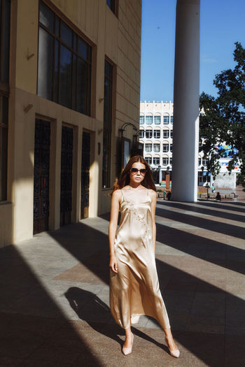 Full length of fashionable young woman standing by building in city