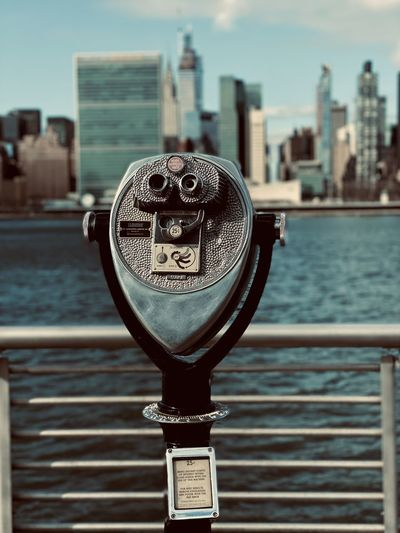 Close-up of coin-operated binoculars against river in city