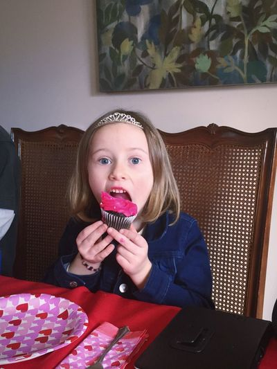 Portrait Of Girl Eating Cupcake At Home