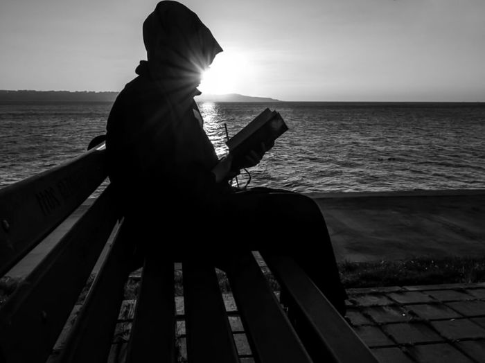 Man sitting by sea against sky during sunset