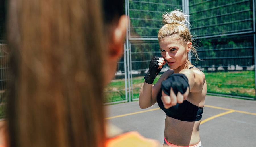 Portrait of female athlete exercising with friend on court against fence
