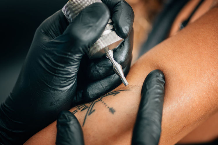 Cropped Image Of Person Tattooing On Hand