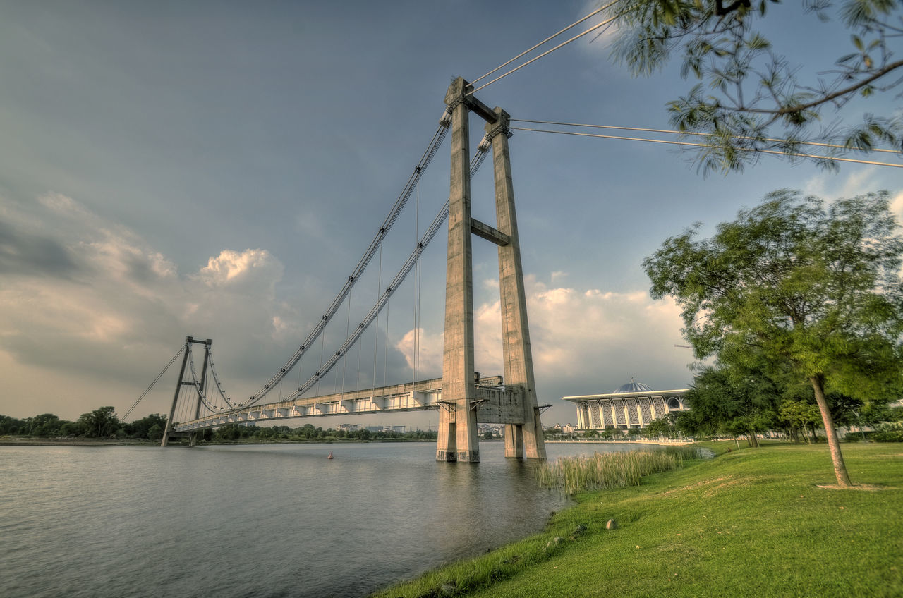 Suspension Bridge Over River Against Cloudy Sky
