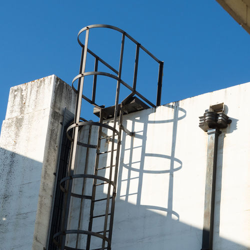 Dual Drains Drain Architecture Blue Building Building Exterior Built Structure Clear Sky Day Escape Escape Ladder Ladder Low Angle View Metal No People Outdoors Railing Rainpipe Shadow Sky Sunlight Wall - Building Feature