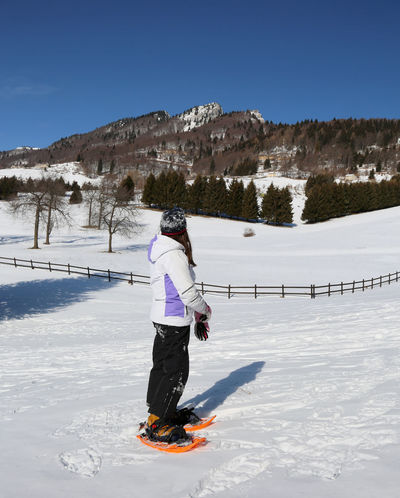 mountains panorama and a little girl wirh sportwear and orange snowshoes in winter Winter Wintertime Adventure Child Cold Temperature Day Girl Leisure Activity Mountain Nature One Person Outdoors Real People Scenics Snow Spitz Sport Sportwear Tonezza Tonezza Del Cimone Vacations Weather Winter Winter Sport Winter Wear