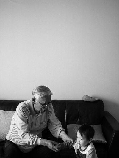 Man Assisting Grandson In Walking While Sitting On Sofa At Home