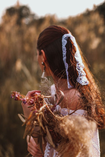 Portrait of brunette women in a white blouse and ribbon with a bouquet of dried flowers in the field
