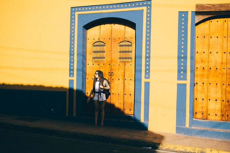Full length portrait of woman standing against yellow building