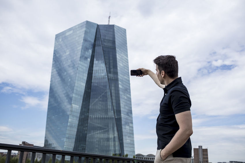 A man taking a picture of a skyscraper in Frankfurt, Germany. Afternoon Architecture Cell Phone Photography Cloud Khaki Pants Low Angle View Man Railing Rear View Reflection Standing Bridge Casual Clothing Caucasian Cell Phone  Golf Shirt Hand In Pocket High Rise Building Male Medium Shot One Person Phone Photography Selfie Sky