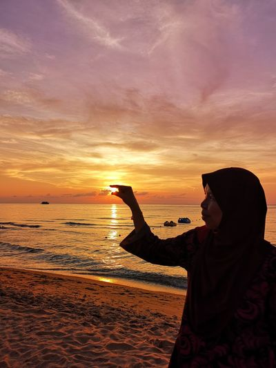 Optical Illusion Of Mid Adult Woman Holding Sun At Beach During Sunset