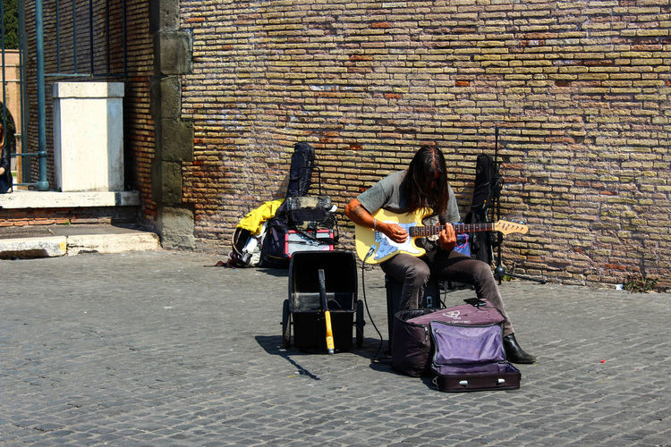 Architecture Brick Wall Casual Clothing Day Full Length Guitar Lifestyles Long Hair Long Hair, Don't Care. Music Outdoors People Real People Rock Rome Sitting Street Art Street Life Street Music Street Musician Street Photography Street Rock Young Adult Moving Around Rome #urbanana: The Urban Playground