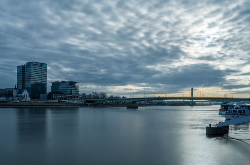 View of the River rhine and the Skyline of Cologne - in Germany 2018. Rhine Futuristic Skyscraper Architecture Bridge Germany Cloudy Dramatic Sky Atmospheric Mood Building Exterior Transportation Built Structure Water Nature River City Cityscape Travel Destinations Waterfront No People Connection Sky Europe Nautical Vessel Outdoors Blue Cloud - Sky Bridge - Man Made Structure Office Building Exterior