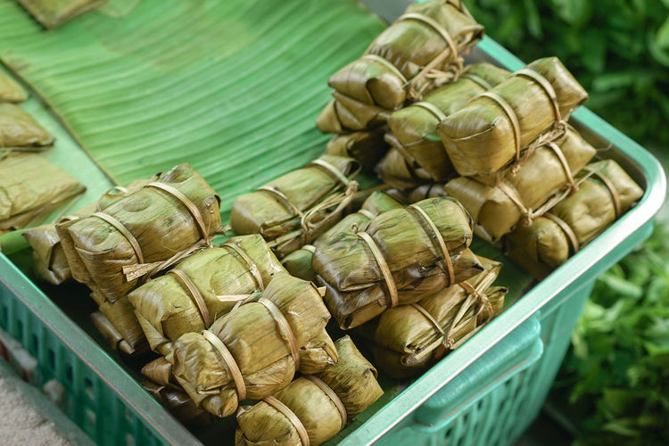 Selective focus on thai dessert of rice porridge wrapped by banana leaf in traditional market.