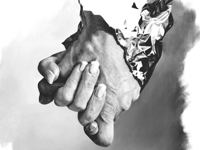 Close-up of man holding hands against sky