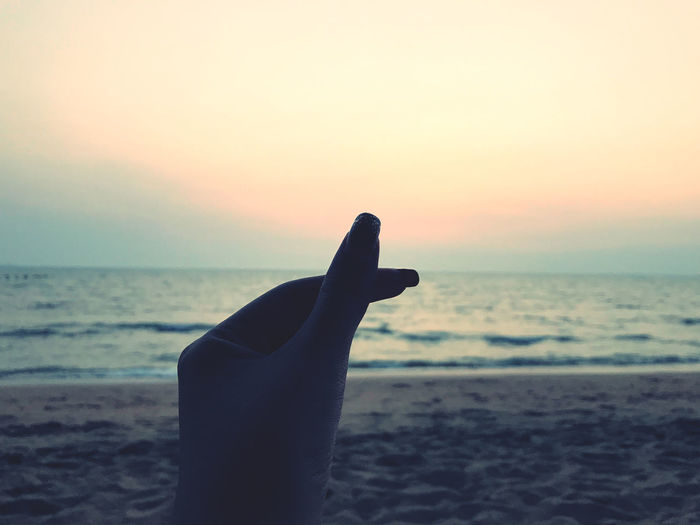 Person hand on sea shore during sunset