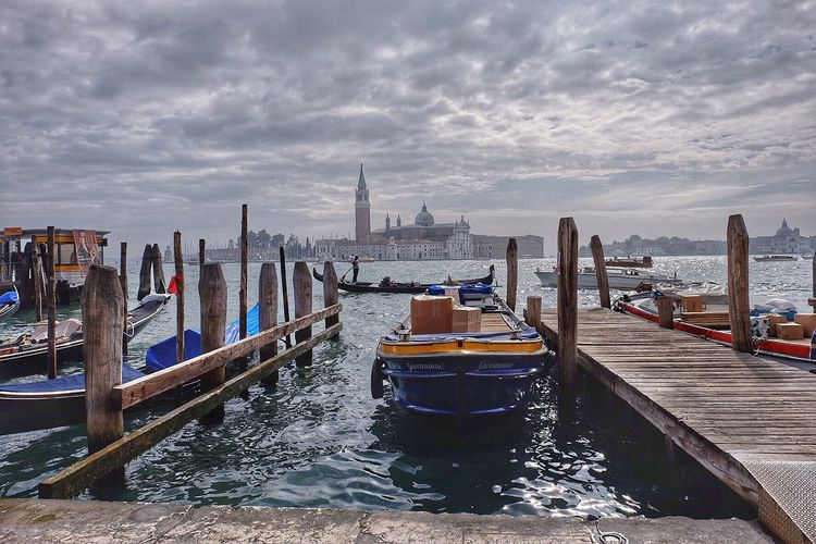 Boats moored at harbor at grand canal against cloudy sky