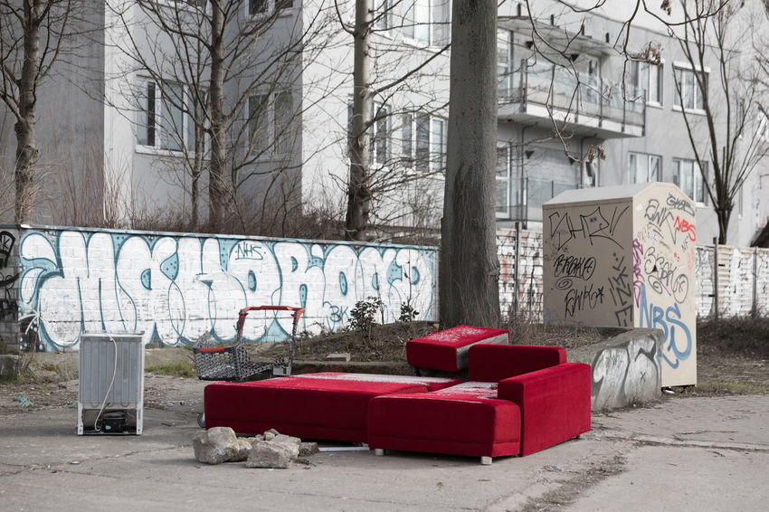 Red, abandoned sofa behind a residential building on an empty parking lot on a cold winterday Container Donation Box Messy Parking Lot Red Abandoned Architecture Building Exterior Built Structure City Clothing Cold Temperature Concrete Block Concrete Wall Garbage Graffiti Isolated Color Outdoors Refrigerator Residential Building Seat Social Issues Sofa Tree Uncultivated