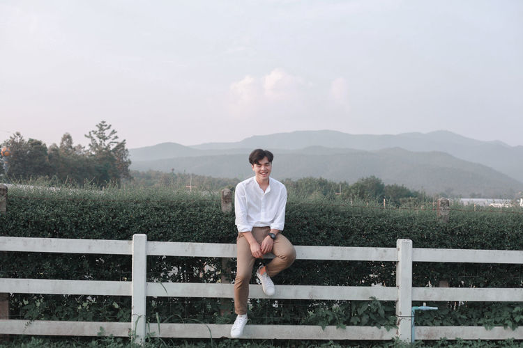 Full length of man standing on railing against sky