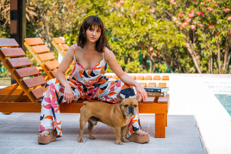 Full length of woman with dog sitting outdoors