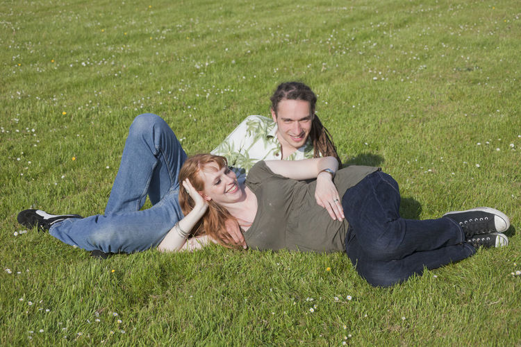 Pregnant Woman With Husband Reclining On Field At Park