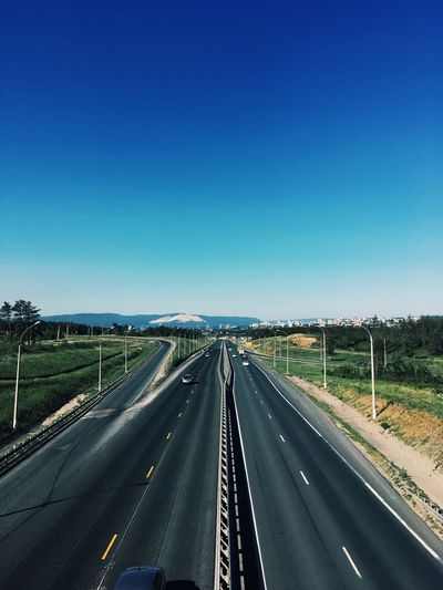 Highway amidst landscape against clear blue sky
