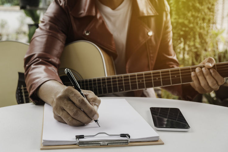 Midsection of man holding guitar on table
