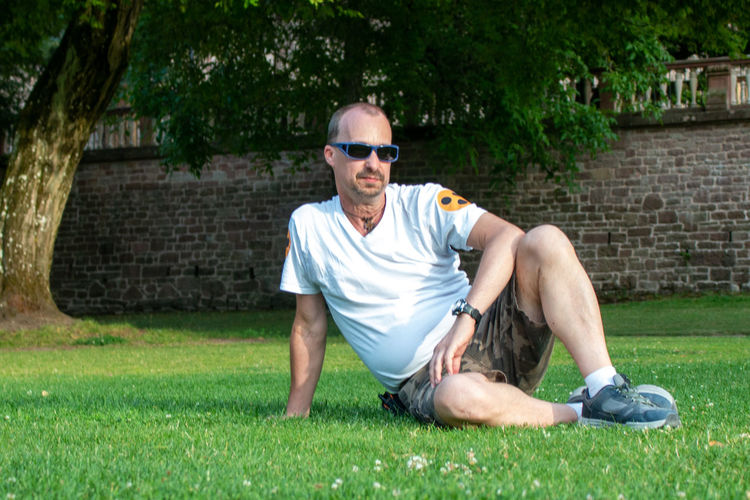 Full length of young man wearing sunglasses while sitting on grass