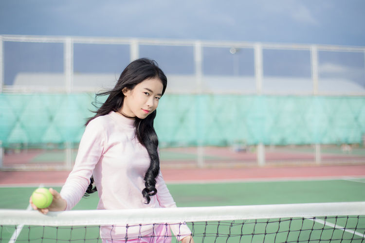 Portrait Of Young Woman Holding Tennis Ball While Standing Against Net On Court