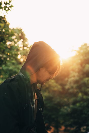 Side View Of Young Man Standing Against Trees