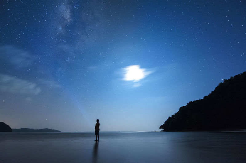 a man stand alone at the beach during summer night. with milky way, moon and stars. Astronomy Beauty In Nature Galaxy Leisure Activity Lifestyles Nature Night One Person Real People Scenics - Nature Sea Silhouette Sky Space Standing Star - Space Tranquil Scene Tranquility Water