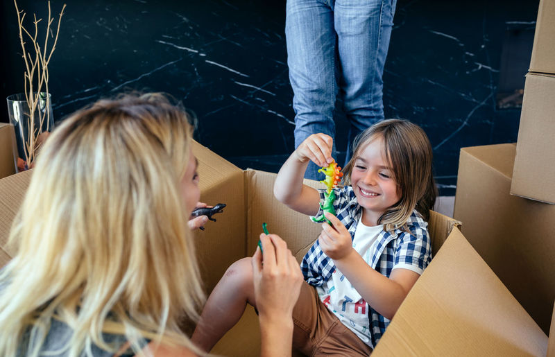 Mother and son playing with toys sitting inside a moving box Family Fun Funny Happiness Happy Horizontal Man Moving Unpacking Woman Boxes Boy Cardboard Home Interior House Indoors  Kid Lifestyles Living Room New Home Packing Placing Playing Real People Relocating