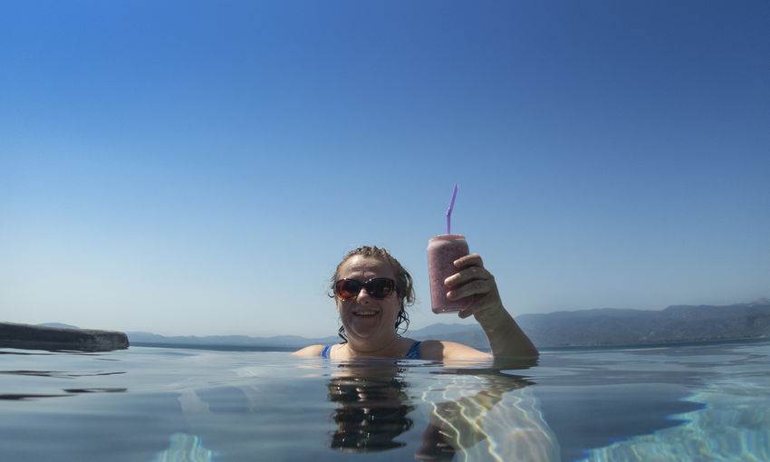 Portrait of woman having drink in swimming pool against clear blue sky