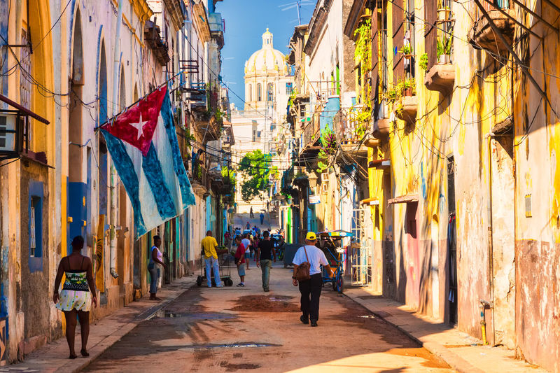 Street scene with cuban flag and old colorful buildings in Havana City Cityscape Cuba Cuba Collection Decay Havana Havana, Cuba Old Havana Old Havana, Cuba Revolution Weathered Architecture Building Caribbean City Colorful Cuban Flag People People Photography Real People Street Street Photography Traditional Urban