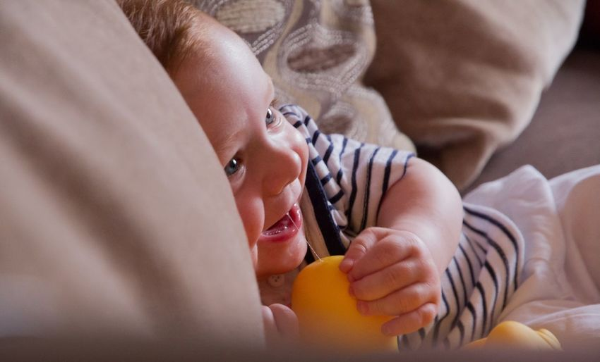 Close-Up Of Smiling Baby Boy Relaxing On Bed At Home