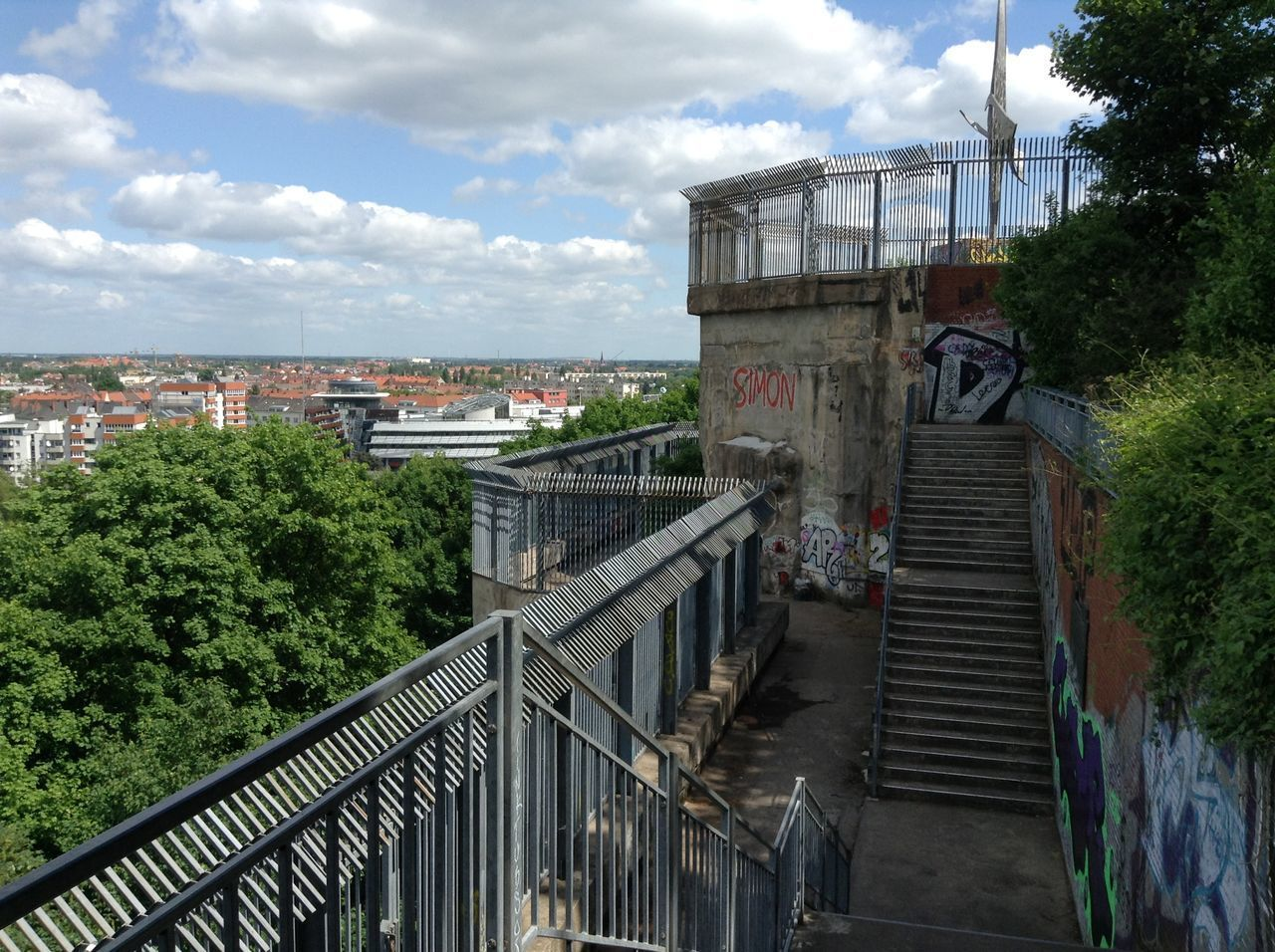 WOMAN STANDING ON STAIRCASE BY BRIDGE IN CITY
