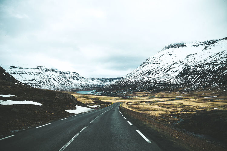 Road leading towards snowcapped mountains against sky