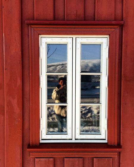 Reflection of man photographing with mobile phone on windows of house