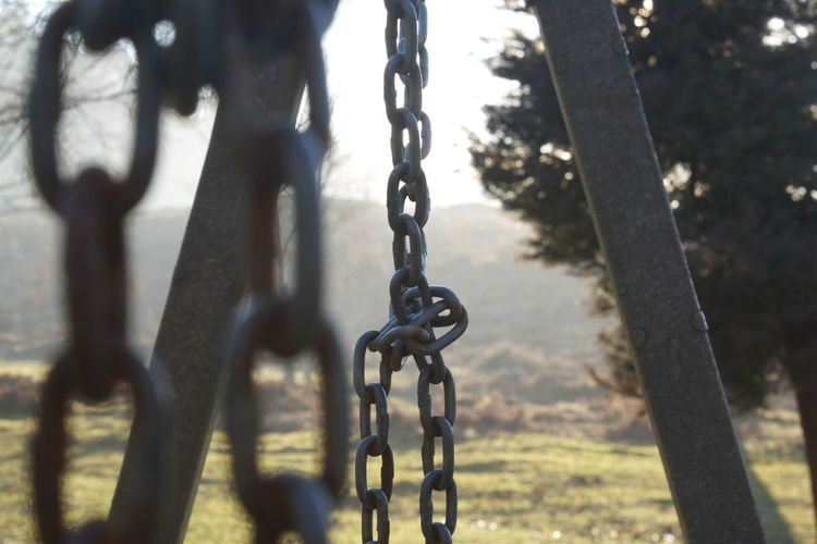 Chains in knots. Chain Close-up Connection Day Field Hanging Metal Nature No People Outdoor Play Equipment Outdoors Park Park - Man Made Space Playground Selective Focus Strength Sunlight Swing