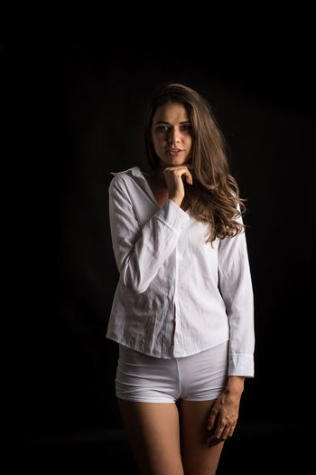 Portrait Looking At Camera Studio Shot One Person Three Quarter Length Young Adult Hair Black Background Standing Indoors  Front View Long Hair Young Women Beautiful Woman Beauty Women Adult Fashion Hairstyle Contemplation
