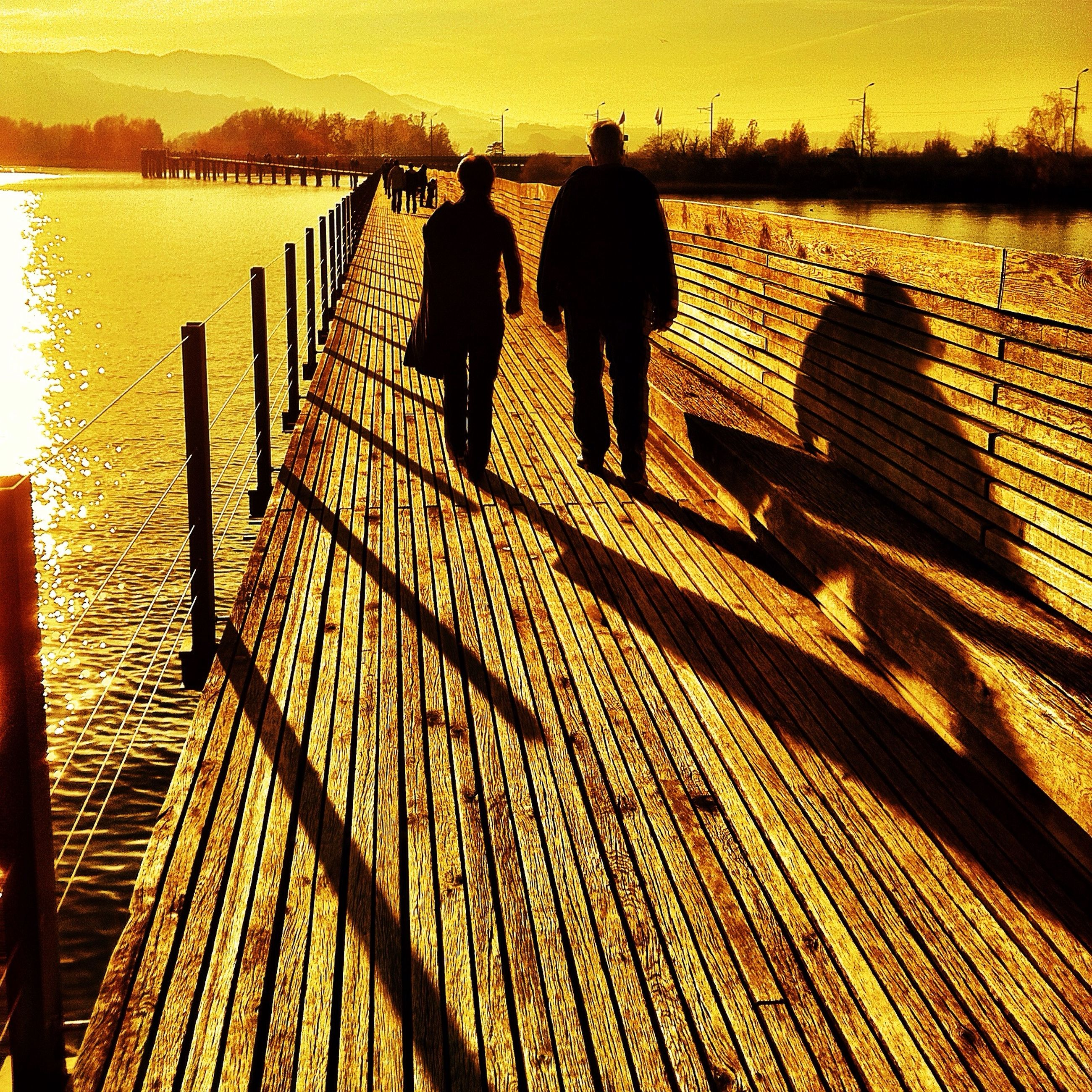 sunset, silhouette, lifestyles, men, water, railing, leisure activity, walking, standing, full length, rear view, pier, person, tranquility, sea, sunlight, nature