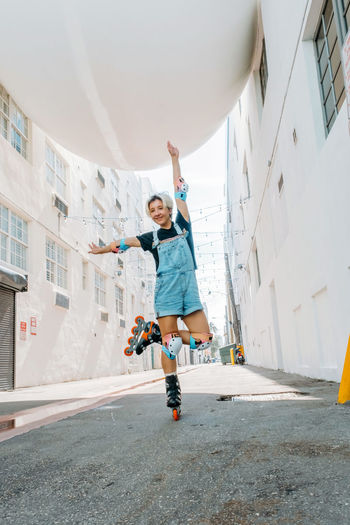 Full length of woman inline skating on road amidst buildings