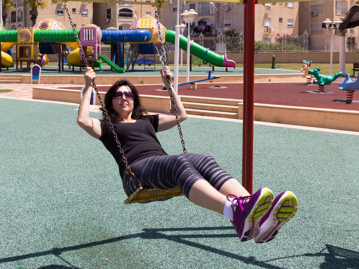 Full length of mature woman swinging at playground