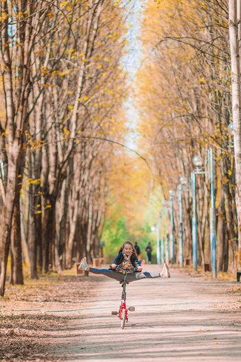 Woman on road amidst trees in forest during autumn