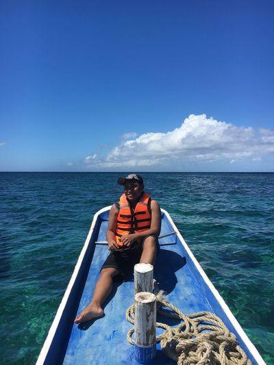 Man Sitting On Boat In Sea Against Blue Sky