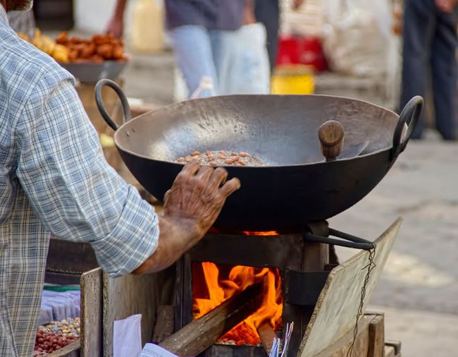Cropped image of vendor roasting peanuts at market