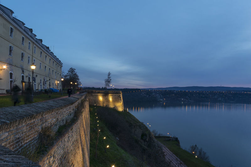 View on Danube river and Petrovaradin fortress walls Danube In Novi Sad, Serbia, Green Petrovaradin Fortress Architecture Blue Sky Blurred Motion Building Exterior Building Lights Built Structure City Cliffs And Water Colors Of Nature Danube River Fortress In Europe Illuminated Medieval Architecture Nature Night Outdoors People Passing By Real People Sky Stone Walls Street Light Water