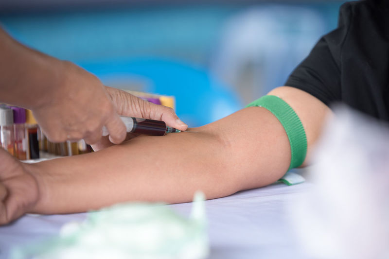 Cropped hands of nurse removing blood from patient arm in hospital