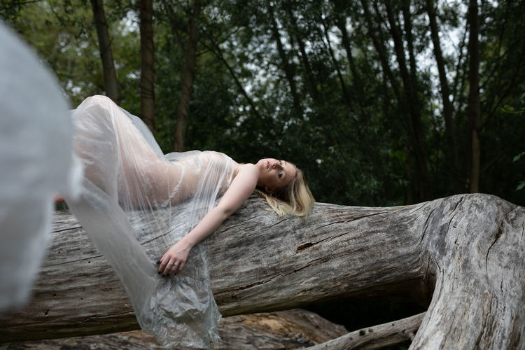 Portrait of naked woman wrapped in a polythene lying down on tree trunk in forest